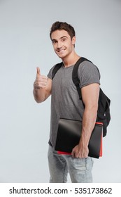 Portrait of a smiling male student with backpack showing thumbs up over white background