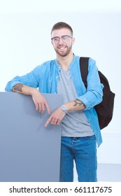 Portrait of a smiling male student holding blank board. Educatio