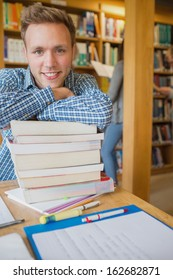 Portrait of a smiling male student with stack of books while others in background at the college library