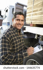 Portrait of a smiling male supervisor with clipboard by truck loaded with wood