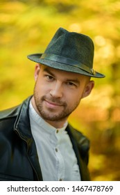 Portrait of a smiling man in a black hat and leather jacket on a yellow autumn background looking at the camera. Autumn background. Smiling young man. Vertical photo
