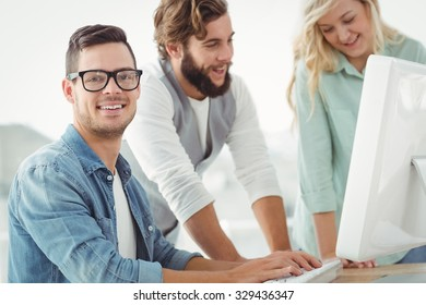 Portrait of smiling man with colleagues discussing at computer desk in office