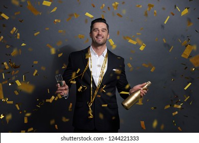 Portrait of smiling man drinking alcohol at studio shot