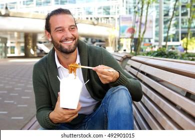 Portrait of smiling man eating chinese take away food