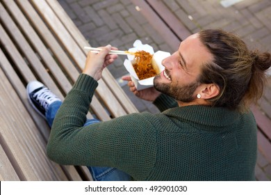 Portrait of smiling man eating chinese food with chopsticks on bench