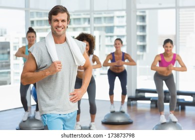 Portrait of a smiling man with fit people performing step aerobics exercise in gym