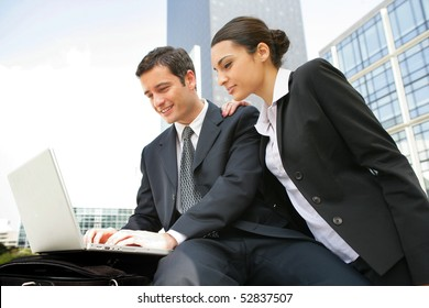 Portrait of a smiling man in front of a laptop computer and a woman