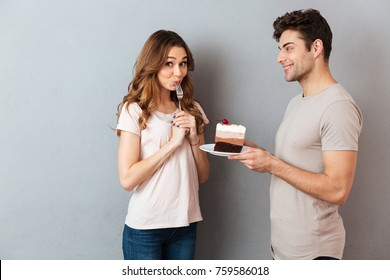 Portrait of a smiling man giving his girlfriend a piece of cake on a plate isolated over gray wall background
