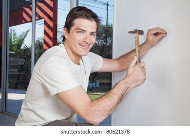 Portrait of smiling man hammering the wall with nail