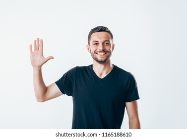 Portrait of smiling man with hand raised in greeting. High five concept