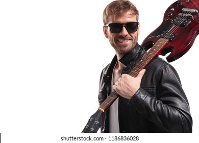 portrait of smiling man holding electric guitar on shoulder looking to side while standing on white background
