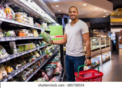 Portrait of smiling man holding spinach at supermarket. Young african man with shopping basket and vegetable in grocery store. Happy black guy buying food at grocery shop and looking at camera.