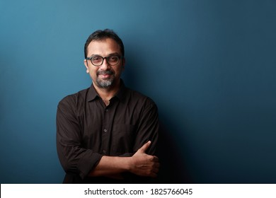 Portrait of a smiling man of Indian ethnicity against a blue wall background.