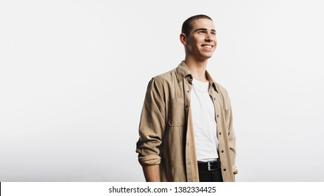 Portrait of smiling man isolated on white background. Young man wearing an unbuttoned shirt looking away.