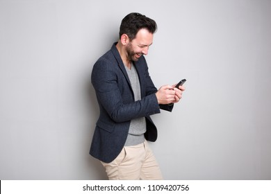 Portrait of smiling man looking at text message on mobile phone