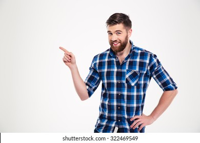 Portrait of a smiling man pointing finger away isolated on a white background