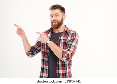 Portrait of a smiling man pointing fingers away isolated on a white background