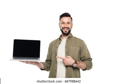 portrait of smiling man pointing at laptop with blank screen isolated on white
