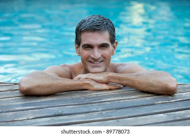 Portrait of smiling man relaxing by the swimming pool's edge