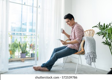 Portrait of a smiling man relaxing on chair new window using table and holding coffee cup.