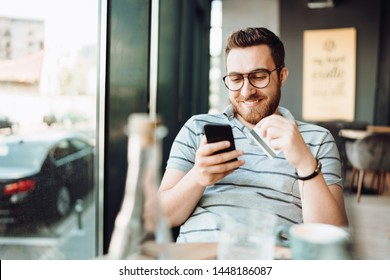 Portrait of smiling man shopping online with smartphone and paying by credit card