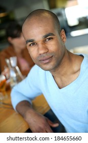 Portrait of smiling man sitting in snack bar