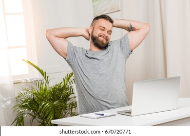 portrait of smiling man sitting at workplace with laptop at home