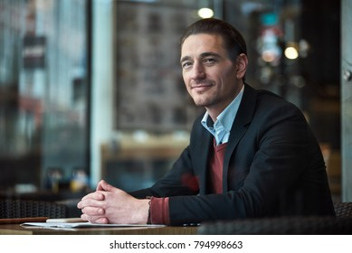 Portrait of smiling man situating at desk in confectionary shop. Relax concept