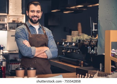 Portrait of smiling man situating at table while having job in confectionary shop. Occupation concept. Copy space