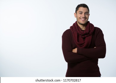 Portrait of smiling man standing with arms crossed against white background