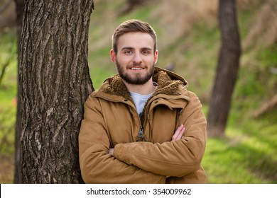Portrait of a smiling man standing with arms folded outdoors and looking at camera