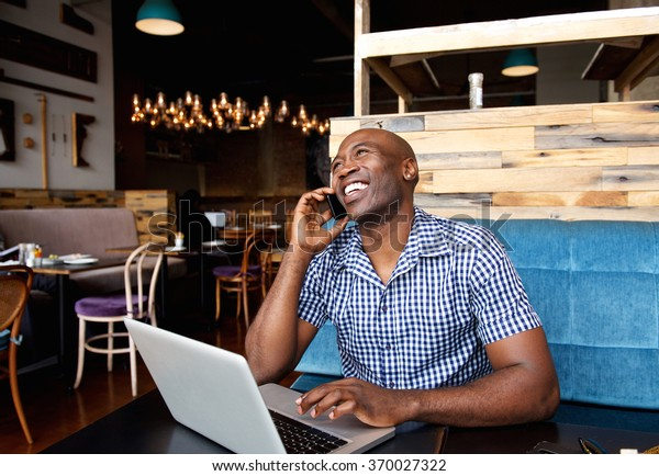Portrait of smiling man talking on cell phone while sitting at a cafe with a laptop