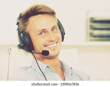 Portrait smiling  man talking using hands-free set at customer service office