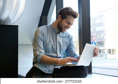Portrait of a smiling man using laptop