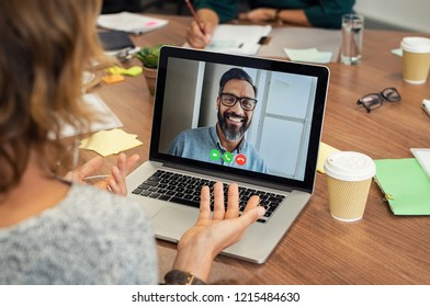 Portrait of smiling man video conferencing on laptop with businesswoman. Woman video conferencing with mature middle eastern businessman on laptop. Happy man in video call with colleague over laptop.