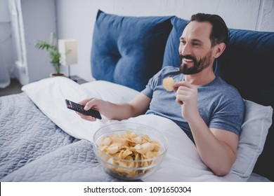 Portrait of smiling man watching tv and eating chips while resting in the bed at home