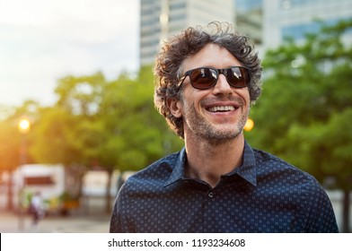 Portrait of smiling man wearing sunglasses and looking away in the city streets. Cheerful mature businessman walking with a big smile on face. Happy man in blue shirt and glasses enjoying the sunset.