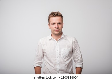 Portrait of a smiling man in white shirt on simple background.