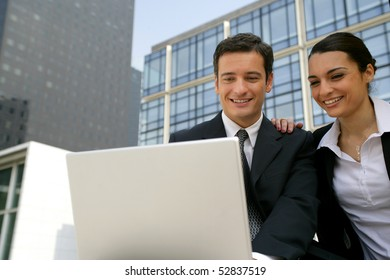 Portrait of  smiling man and woman in front of a laptop computer