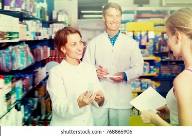 Portrait of smiling man and woman pharmacists in white coat in pharmacy