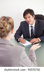 Portrait of a smiling manager interviewing a female applicant in an office