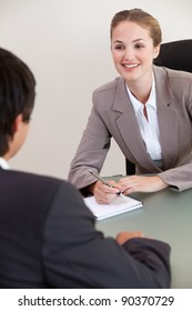 Portrait of a smiling manager interviewing a male applicant in her office