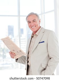 Portrait of a smiling manager reading newspaper in the office