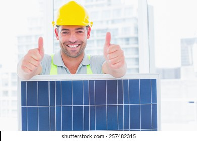 Portrait of smiling manual worker with solar panel gesturing thumbs up in bright office