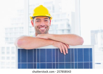 Portrait of smiling manual worker with solar panel in bright office