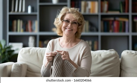 Portrait of smiling mature 60s grandmother sit on couch in living room knitting using needles, happy middle-aged 70s woman relax at home do favorite hobby activity on weekend, wellbeing concept