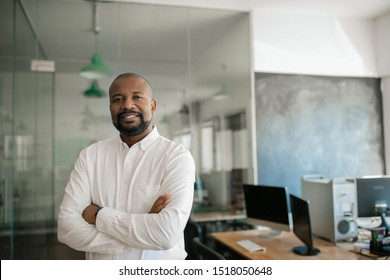 Portrait of a smiling mature African American businessman standing with his arms crossed in a large modern office in the late afternoon