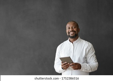 Portrait of a smiling mature African American businessman using a digital tablet while standing in front of a blank office chalkboard