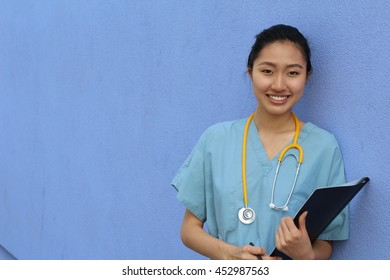 Portrait of smiling mature Asian doctor with stethoscope isolated over blue background with copy space