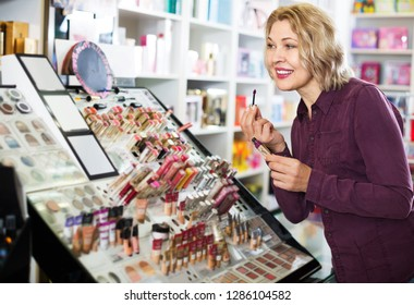 Portrait of smiling mature blondie selecting lip gloss in store